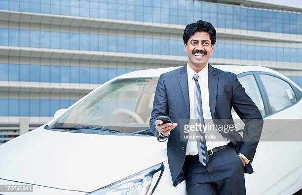 South Indian businessman text messaging on a mobile phone in front of a car