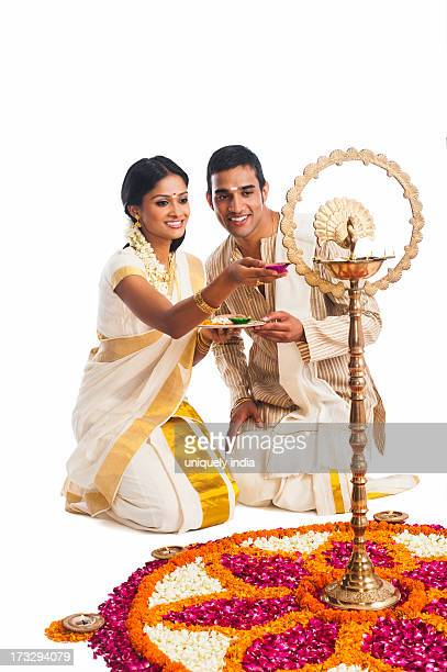 South Indian couple lighting oil lamp at Onam