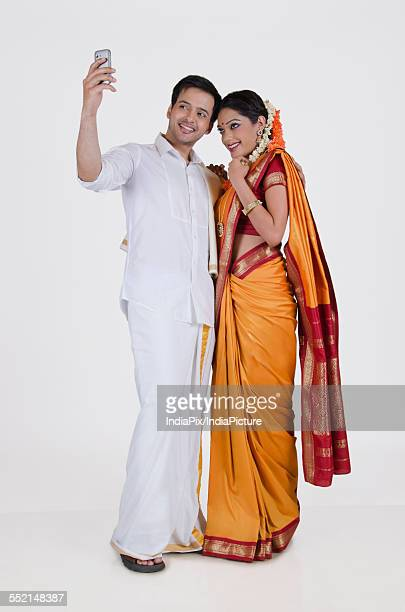 South Indian couple looking at a mobile phone