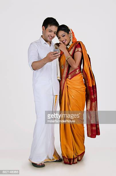 South Indian couple looking at an sms on a mobile phone