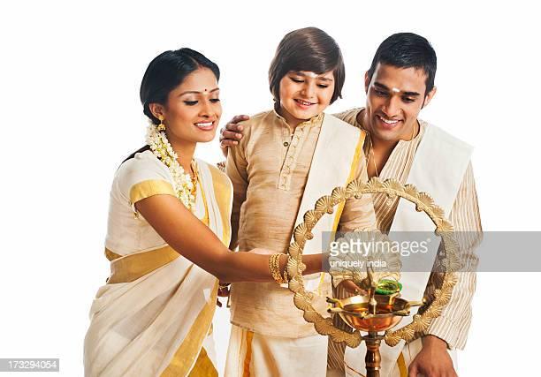 South Indian family lighting oil lamp at Onam
