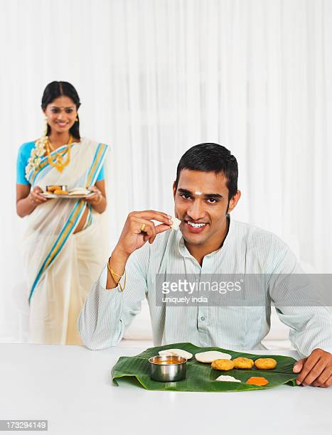 South Indian man eating food with his wife in the background