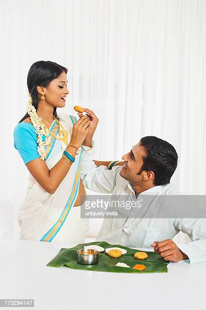 South Indian man feeding food to his wife