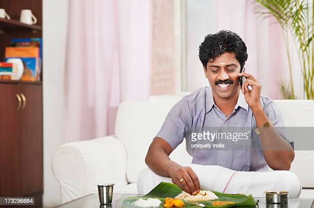 South Indian man having food and talking on a mobile phone