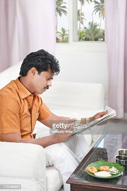 South Indian man reading a newspaper and having breakfast