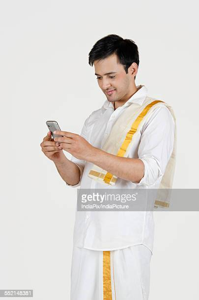 South Indian man reading an sms on a mobile phone