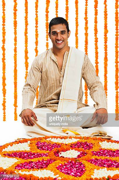 South Indian man sitting near a rangoli of flowers at Onam