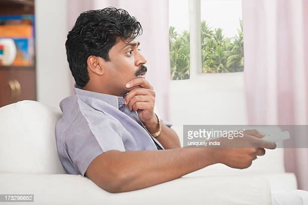 South Indian man watching TV and looking surprised