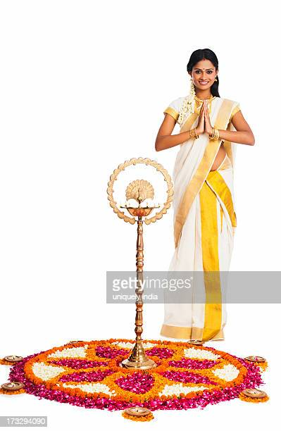 South Indian woman greeting near rangoli of flowers at Onam