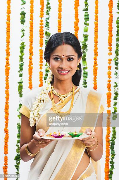 South Indian woman holding a puja thali at Onam