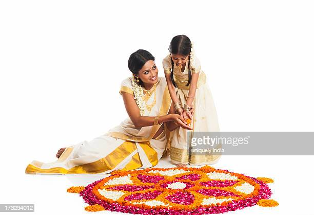 South Indian woman making a rangoli of flowers with her daughter at Onam