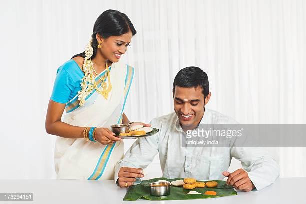 South Indian woman serving food to her husband