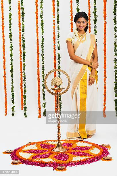 South Indian woman standing near rangoli of flowers at Onam