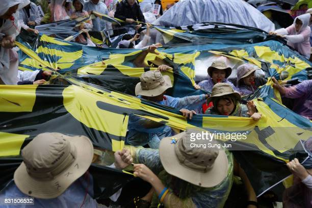 South Korea activists tear antiJapan placard during a 72nd Liberation Day rally in front of Japanese embassy on August 15 2017 in Seoul South Korea...