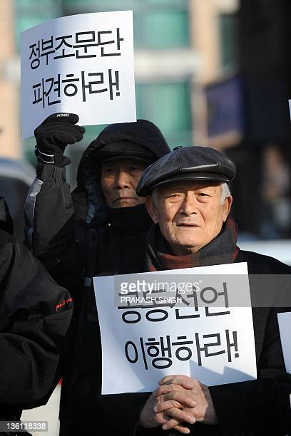 South Korea opposition group activists hold placards during a protest in Seoul on December 27 demanding official government condolence delegation...