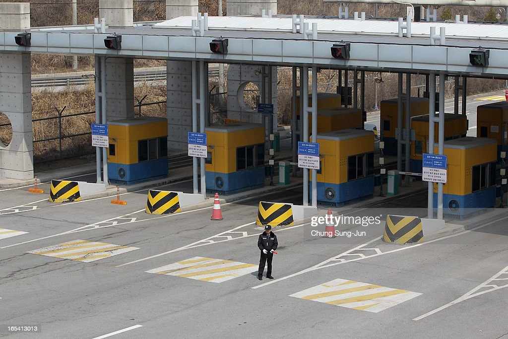 A South Korea security guard stands on the empty road connection Kaesong Industrial Complex (KIC) with South's CIQ (Customs, Immigration, Quarantine) at inter-Korean transit office on April 4, 2013 in Paju, South Korea. 400 South Koreans remain in the joint industrial complex fearing they can not get back there once return to South. In recent weeks North Korea have threatened to attack South Korea and U.S. military bases.