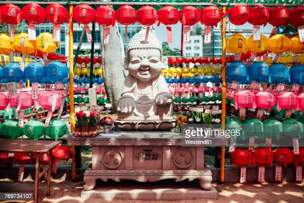 South Korea, Seoul, Happy Buddha statue surrounded by colorful lanterns at Jogyesa Temple