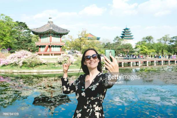 South Korea, Seoul, Woman taking a selfie with smartphone at Gyeongbokgung Palace