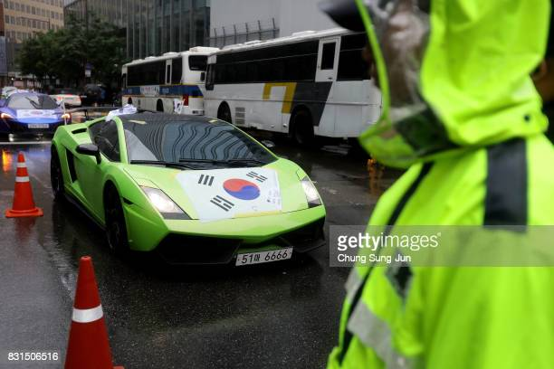 South Korea stands next to a Lamborghini wearing South Korean national flag in front of Japanese embassy during a 72nd Liberation Day rally in front...