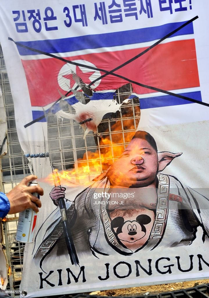 A South Korean activist burns a placard showing a caricature of North Korean leader Kim Jong-Un during an anti-North Korea rally in Seoul on April 18, 2013. North Korea laid out conditions on April 18 for any talks with Seoul or Washington, including the withdrawal of UN sanctions and a guaranteed end to South Korea-US joint military drills. AFP PHOTO / JUNG YEON-JE