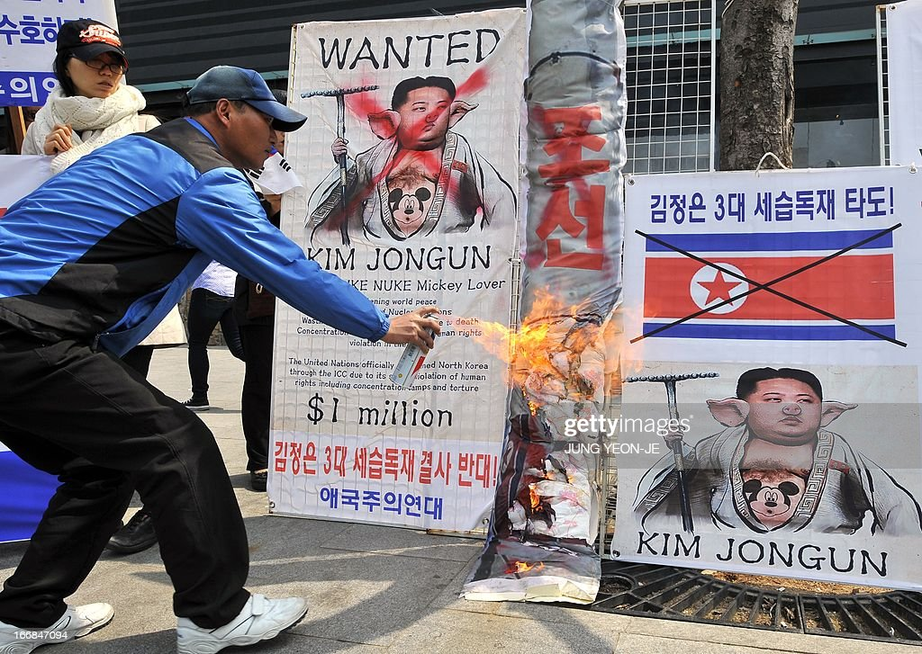 A South Korean activist burns placards showing a caricature of North Korean leader Kim Jong-Un during an anti-North Korea rally in Seoul on April 18, 2013. North Korea laid out conditions on April 18 for any talks with Seoul or Washington, including the withdrawal of UN sanctions and a guaranteed end to South Korea-US joint military drills.