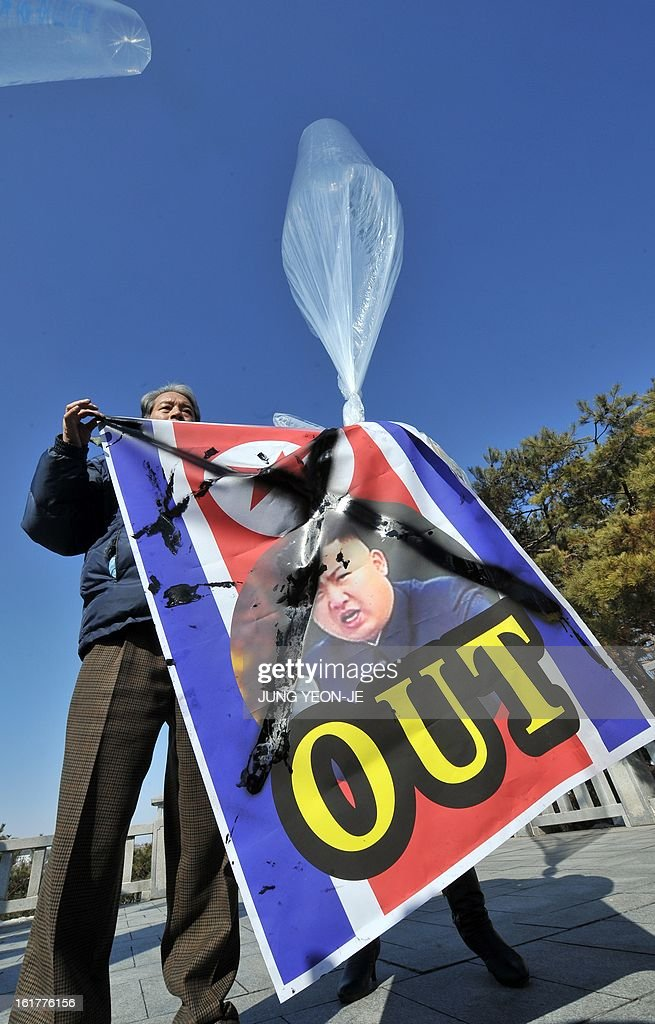 A South Korean activist holds a banner showing a portrait of North Korean leader Kim Jong-Un hanging on a balloon at Imjingak park near the inter-Korean border in Paju on February 16, 2013. Activists launched balloons across the border carrying leaflets that criticise North Korea's ruling Kim family on the birth anniversary of late leader Kim Jong-Il, amid high tension over its long-range rocket launch and nuclear test.