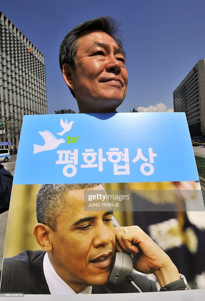 A South Korean activist holds a placard reading 'peace talks' while showing a picture of US President Barack Obama during an anti-war rally urging peace talks with North Korea in Seoul on April 9, 2013. North Korean workers failed to report to work on April 9 at the joint Kaesong industrial zone with South Korea after Pyongyang suspended operations, upping the pressure on Seoul in an escalating military crisis. AFP PHOTO / JUNG YEON-JE
