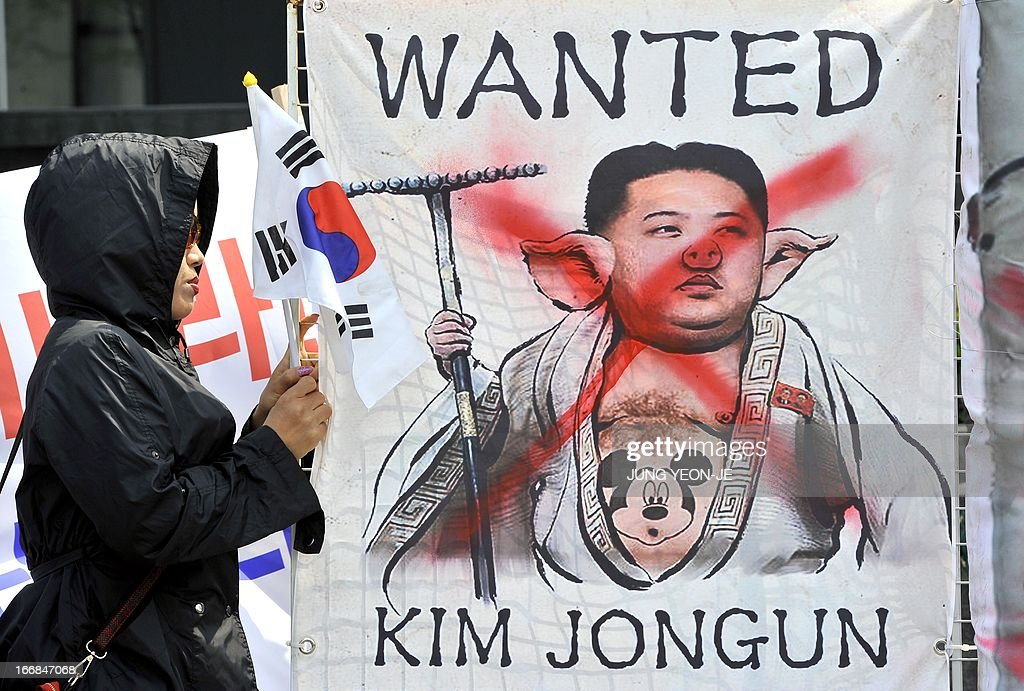 A South Korean activist holds a placard showing a caricature of North Korean leader Kim Jong-Un during an anti-North Korea rally in Seoul on April 18, 2013. North Korea laid out conditions on April 18 for any talks with Seoul or Washington, including the withdrawal of UN sanctions and a guaranteed end to South Korea-US joint military drills. AFP PHOTO / JUNG YEON-JE