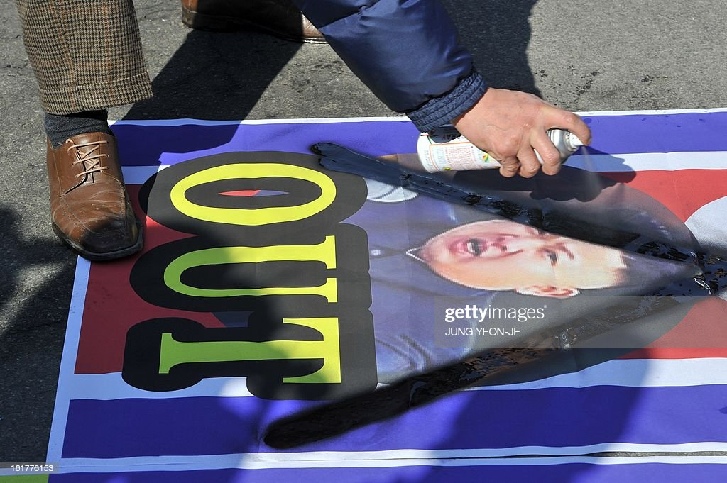 A South Korean activist spray paints a cross over a portrait of North Korean leader Kim Jong-Un as former North Korean defectors launch balloons carrying anti-Pyongyang leaflets at Imjingak park near the inter-Korean border in Paju on February 16, 2013. Activists launched balloons across the border carrying leaflets that criticise North Korea's ruling Kim family on the birth anniversary of late leader Kim Jong-Il, amid high tension over its long-range rocket launch and nuclear test. AFP PHOTO / JUNG YEON-JE