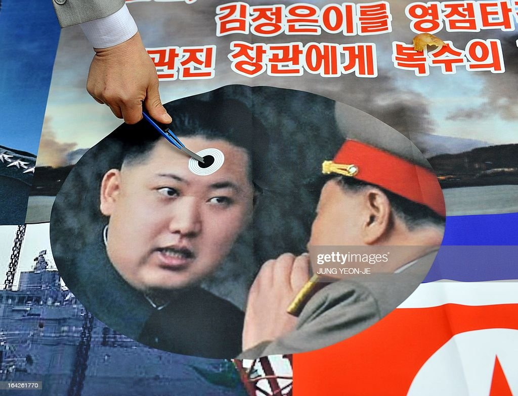 A South Korean activist stabs a pocket knife on a picture of North Korean leader Kim Jong-Un (L) during an anti-North Korea rally near the national assembly in Seoul on March 22, 2013. North Korea posted a new propaganda video on March 22, showing paratroopers descending on Seoul in an invasion scenario that envisages taking around 150,000 US residents in South Korea hostage. AFP PHOTO / JUNG YEON-JE