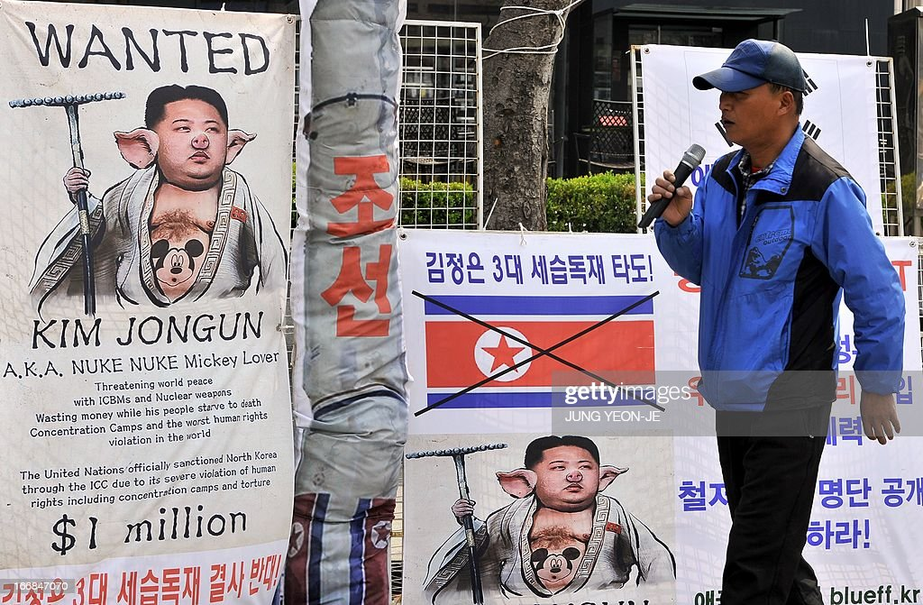 A South Korean activist walks past placards showing a caricature of North Korean leader Kim Jong-Un during an anti-North Korea rally in Seoul on April 18, 2013. North Korea laid out conditions on April 18 for any talks with Seoul or Washington, including the withdrawal of UN sanctions and a guaranteed end to South Korea-US joint military drills.