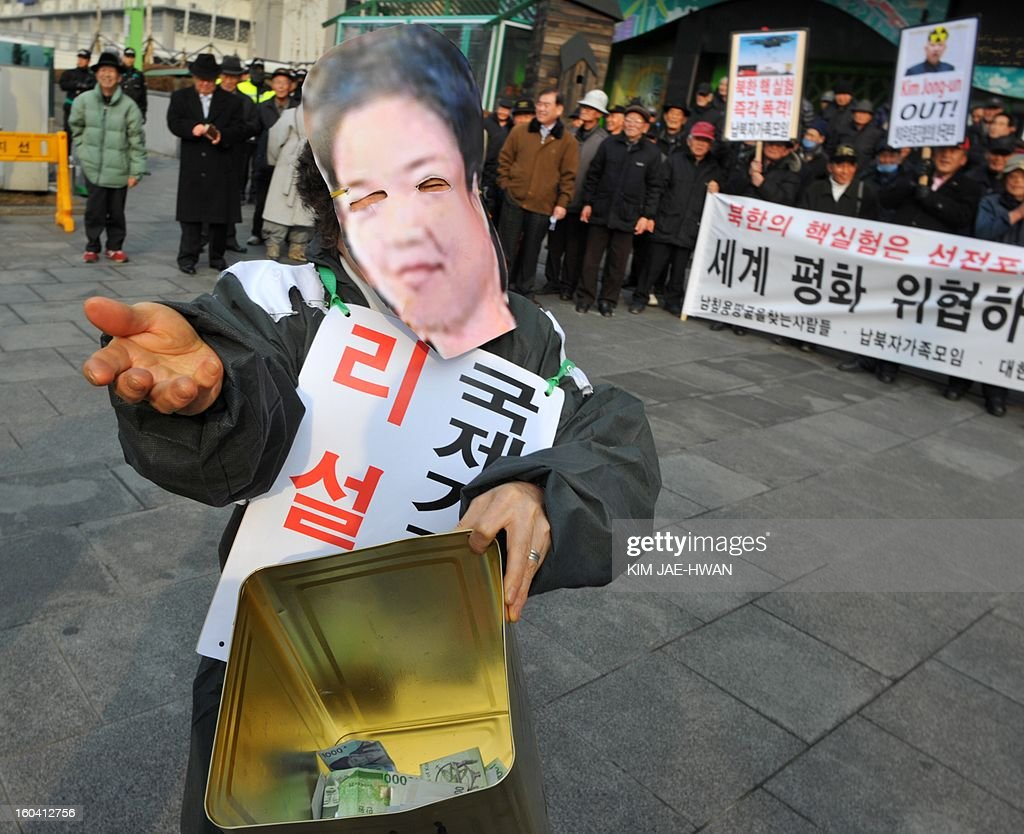 South Korean activist wearing the face mask of North Korean leader Kim Jong-Un's wife Ri Sol-Ju (L) 'begs' for money during an anti-Pyongyang rally urging North Korea to abandon nuclear weapons in Seoul on January 31. South Korean President Lee Myung-Bak held an emergency security meeting on January 31 that warned North Korea of 'serious consequences' if it went through with an expected nuclear test.