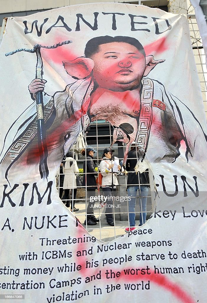 South Korean activists are seen through a burnt hole of a placard showing a caricature of North Korean leader Kim Jong-Un during an anti-North Korea rally in Seoul on April 18, 2013. North Korea laid out conditions on April 18 for any talks with Seoul or Washington, including the withdrawal of UN sanctions and a guaranteed end to South Korea-US joint military drills.