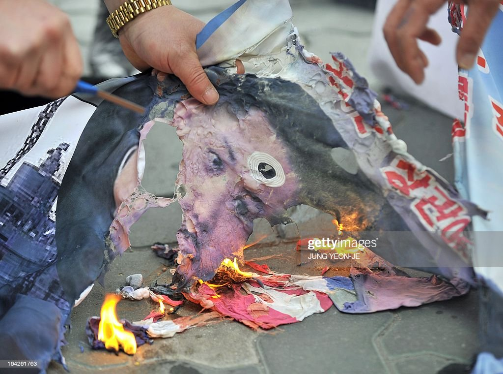 South Korean activists burn a banner showing a picture of North Korean leader Kim Jong-Un during an anti-North Korea rally near the national assembly in Seoul on March 22, 2013. North Korea posted a new propaganda video on March 22, showing paratroopers descending on Seoul in an invasion scenario that envisages taking around 150,000 US residents in South Korea hostage.