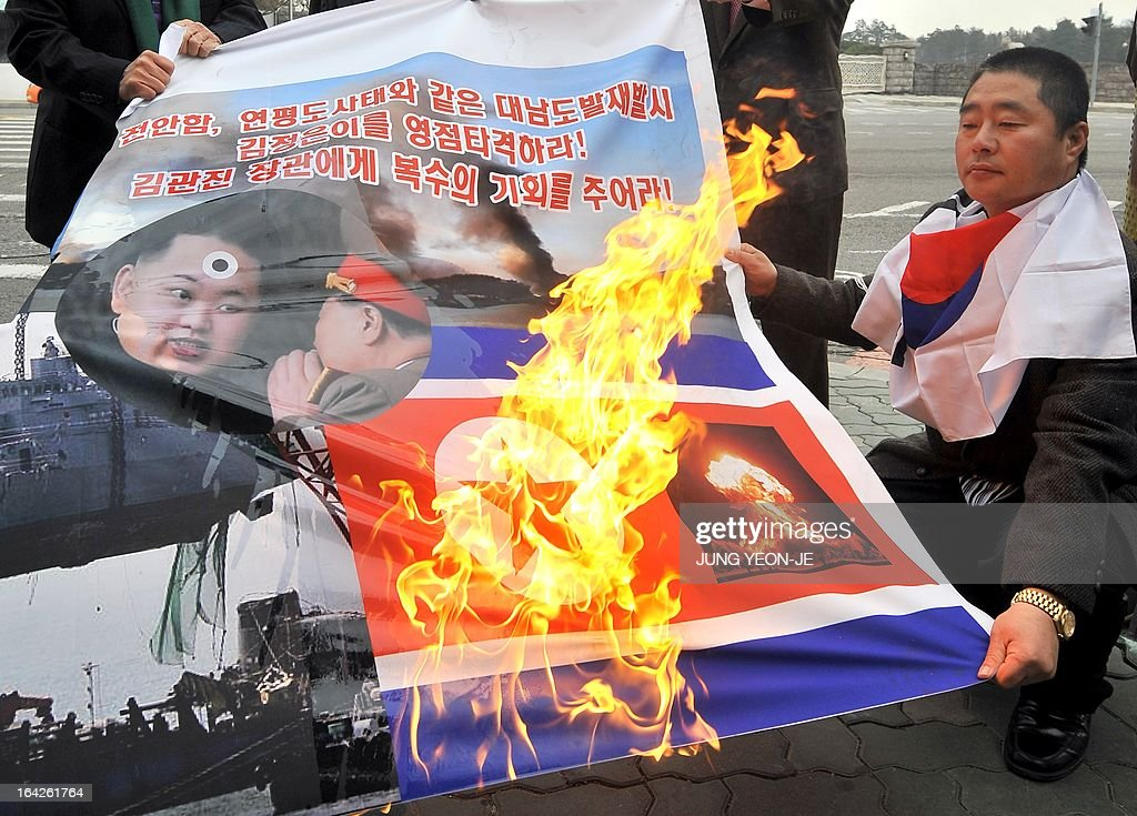 South Korean activists burn a banner showing North Korean flag (R bottom) and North Korean leader Kim Jong-Un (L) during an anti-North Korea rally near the national assembly in Seoul on March 22, 2013. North Korea posted a new propaganda video on March 22, showing paratroopers descending on Seoul in an invasion scenario that envisages taking around 150,000 US residents in South Korea hostage.