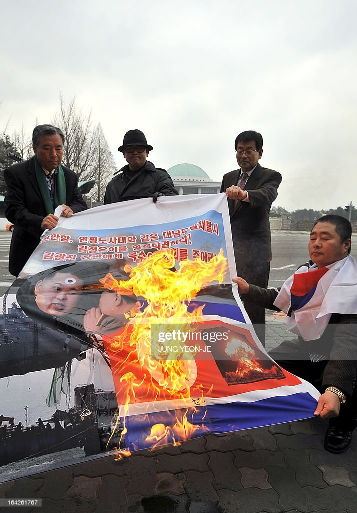 South Korean activists burn a banner showing North Korean flag (R bottom) and North Korean leader Kim Jong-Un (L) during an anti-North Korea rally near the national assembly in Seoul on March 22, 2013. North Korea posted a new propaganda video on March 22, showing paratroopers descending on Seoul in an invasion scenario that envisages taking around 150,000 US residents in South Korea hostage. AFP PHOTO / JUNG YEON-JE