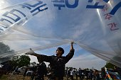 South Korean activists fill gas into a large balloon to launch antiPyongyang leaflets into the air at a field near the Demilitarized zone dividing...