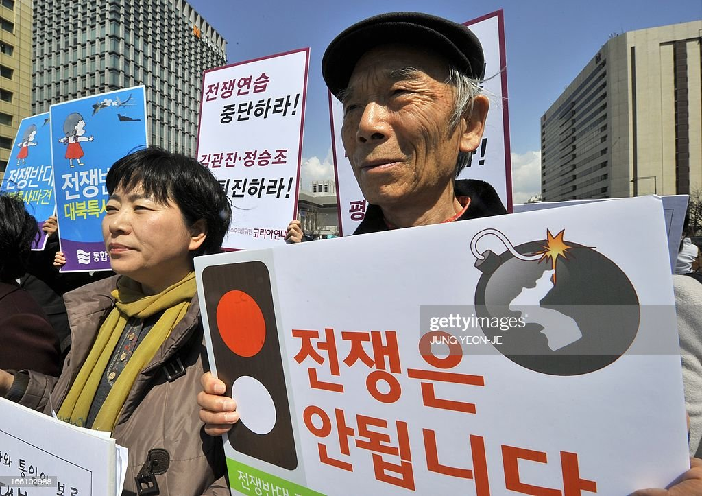 South Korean activists hold placards reading 'We oppose war!' during an anti-war rally urging peace talks with North Korea in Seoul on April 9, 2013. North Korean workers failed to report to work on April 9 at the joint Kaesong industrial zone with South Korea after Pyongyang suspended operations, upping the pressure on Seoul in an escalating military crisis. AFP PHOTO / JUNG YEON-JE