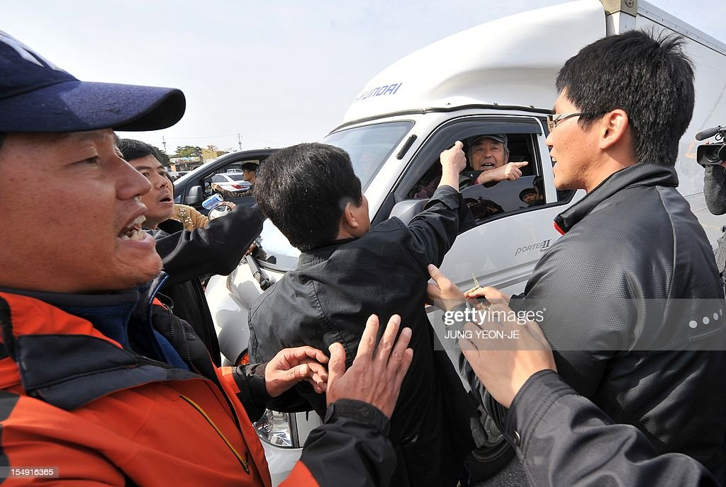 South Korean activists inside a truck schuffle with local residents as plainclothed police officers try to separate them following the launch of anti-North Korea leaflets across the border at a park in the border town of Paju, north of Seoul, on October 29, 2012. A dozen activists floated some 50,000 leaflets across the tense border a week after North Korea threatened military action over a similar propaganda exercise.