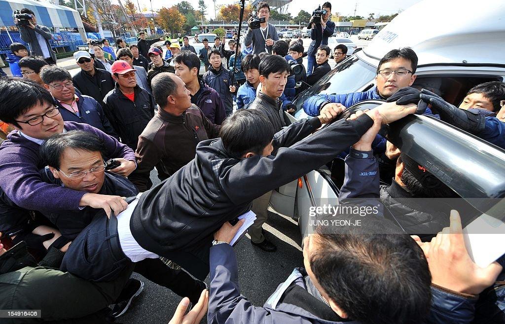 South Korean activists inside a truck (R) schuffle with local residents (L) as plainclothed police officers try to separate them following the launch of anti-North Korea leaflets across the border at a park in the border town of Paju, north of Seoul, on October 29, 2012. A dozen activists floated some 50,000 leaflets across the tense border a week after North Korea threatened military action over a similar propaganda exercise.