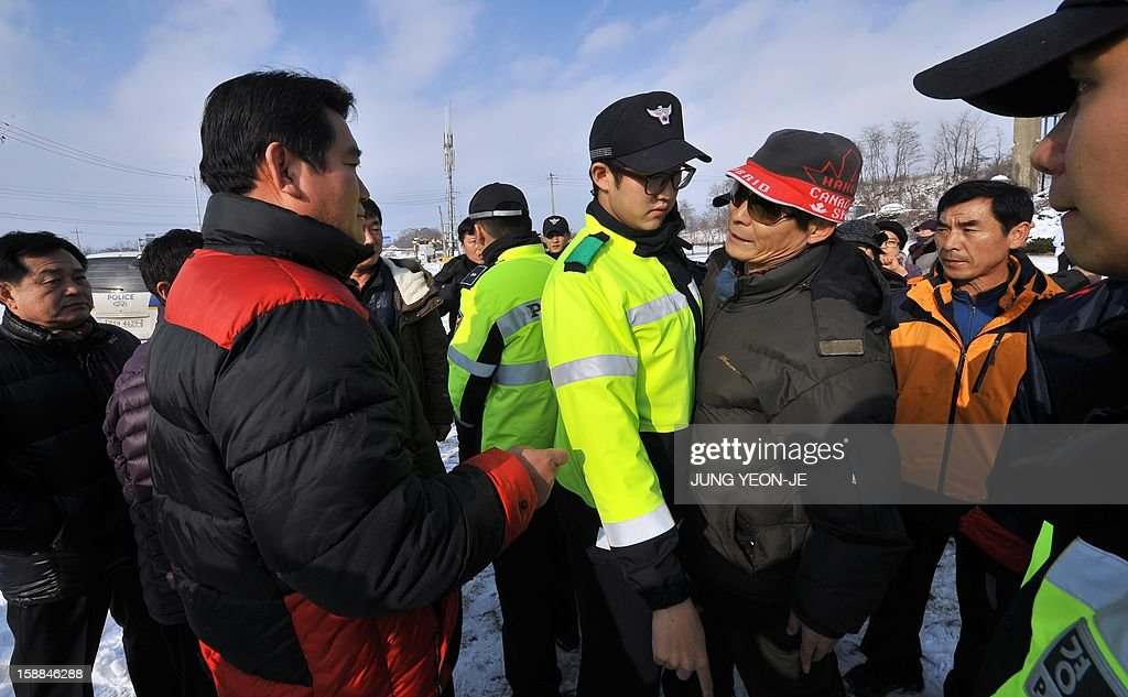 South Korean activists schuffle with local residents (L) who voiced fear of North Korean reprisals as policemen (C) try to separate them following the launch of anti-North Korea leaflets across the border in front of former North Korean Labor Party Cheorwon office building in the South Korean border county of Cheorwon on January 1, 2013. About 30 activists released seven balloons carrying 28,000 leaflets shouting 'Down with North Korea's dynastic dictorship!'. AFP PHOTO / JUNG YEON-JE