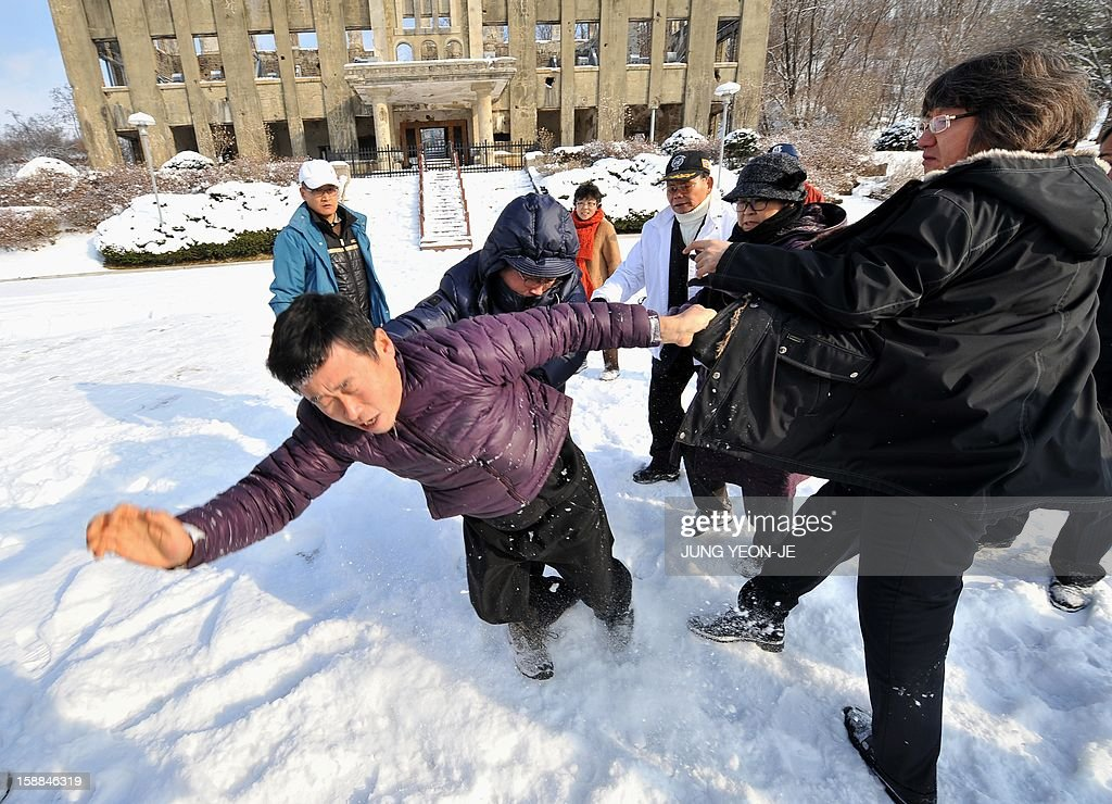 South Korean activists schuffle with local residents (L) who voiced fear of North Korean reprisals following the launch of anti-North Korea leaflets tied to balloons across the border, in front of former North Korean Labor Party Cheorwon office building in the South Korean border county of Cheorwon on January 1, 2013. About 30 activists released seven balloons carrying 28,000 leaflets shouting 'Down with North Korea's dynastic dictorship!'.