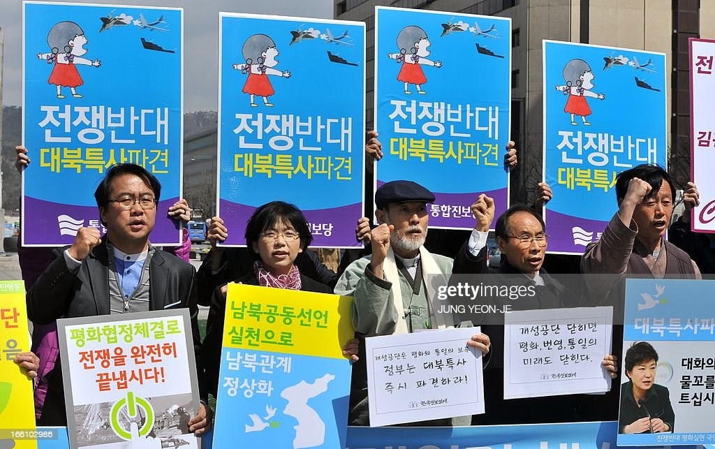 South Korean activists shout slogans during an anti-war rally urging peace talks with North Korea in Seoul on April 9, 2013. North Korean workers failed to report to work on April 9 at the joint Kaesong industrial zone with South Korea after Pyongyang suspended operations, upping the pressure on Seoul in an escalating military crisis. Placards over their heads read 'We oppose war!' and 'Dispatch a special envoy to North Korea!'