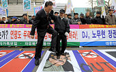 South Korean activists trample a portrait of Kim JungIl during a protest outside the Defense Ministry in Seoul on November 24 denouncing North...