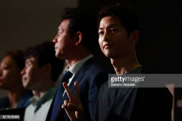 South Korean actor Song Joongki gestures at fans during The Battleship Island red carpet at The MasterCard Theatres at Marina Bay Sands on August 8...