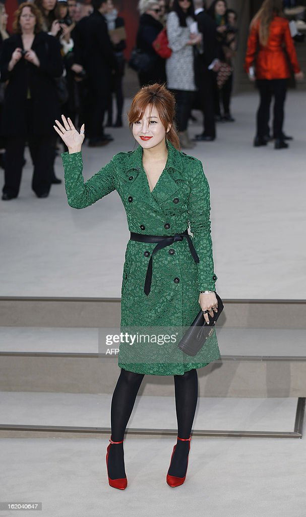 South Korean actress Kim Hee-Sun poses for pictures as she arrives for the Burberry Prorsum 2013 Autumn/Winter catwalk show at London Fashion Week in central London on February 18, 2013.
