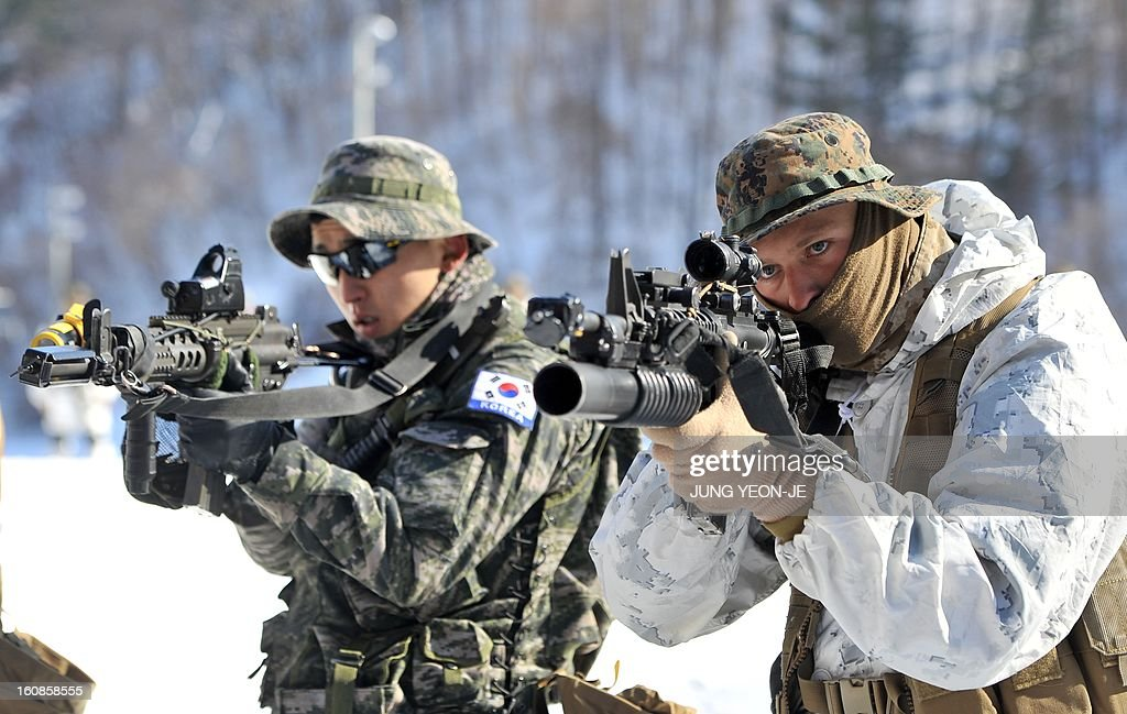South Korean (L) and US (R) Marines aim their weapons during a joint winter drill in Pyeongchang, some 180 kilometers east of Seoul, on February 7, 2013. Marines from South Korea and the United States took part in a military winter drills, which began on February 4 and run through February 22, to test their limits in extreme conditions.