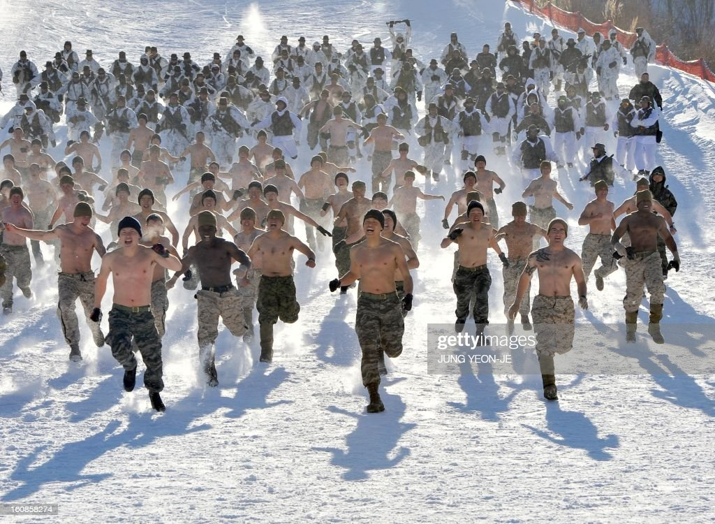 South Korean and US Marines run on a snowy hill during a joint winter drill in Pyeongchang, some 180 kilometers east of Seoul, on February 7, 2013. Marines from South Korea and the United States took part in a military winter drills, which began on February 4 and run through February 22, to test their limits in extreme conditions. AFP PHOTO / JUNG YEON-JE