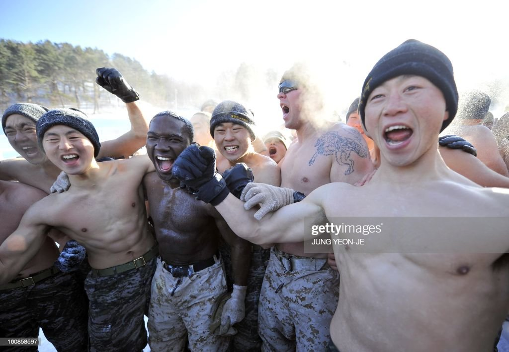 South Korean and US Marines shout together during a joint winter drill in Pyeongchang, some 180 kilometers east of Seoul, on February 7, 2013. Marines from South Korea and the United States took part in a military winter drills, which began on February 4 and run through February 22, to test their limits in extreme conditions. AFP PHOTO / JUNG YEON-JE