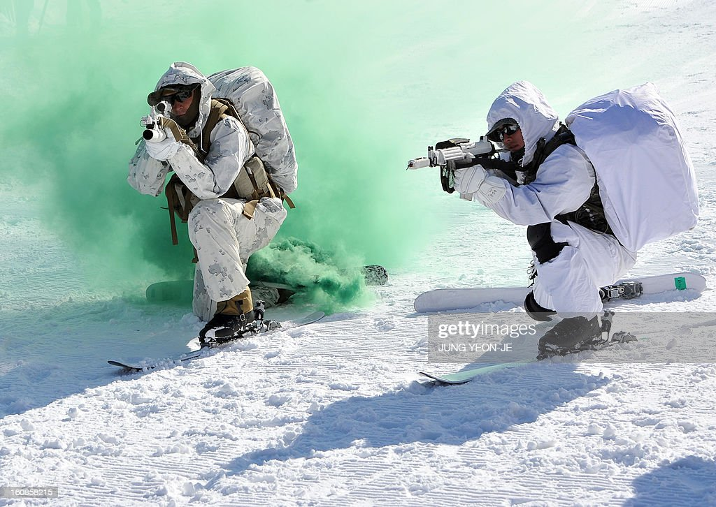 South Korean (R) and US (L) Marines take aim on a hill during a joint winter drill in Pyeongchang, some 180 kilometers east of Seoul, on February 7, 2013. Marines from South Korea and the United States took part in a military winter drills, which began on February 4 and run through February 22, to test their limits in extreme conditions.